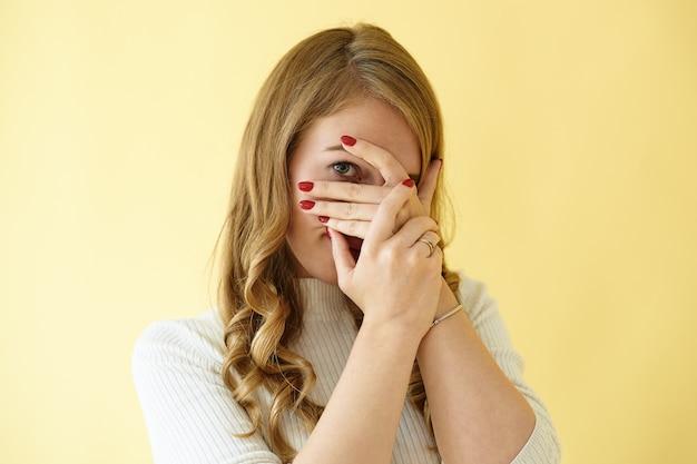 Na białym tle strzał studyjny uroczej, stylowej młodej europejki z czerwonymi wypielęgnowanymi paznokciami zakrywającymi twarz rękami i zaglądającą przez palce do kamery, czując się nieśmiała, zawstydzona lub przestraszona
