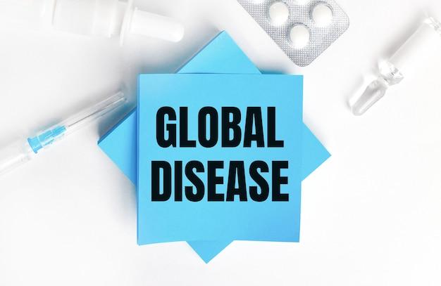 Na białym tle strzykawka, ampułka, pigułki, fiolka z lekiem oraz jasnoniebieskie naklejki z napisem global disease. koncepcja medyczna