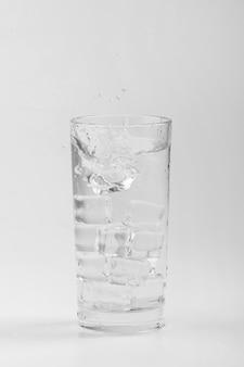 Na białym tle szklanka wody z cieniami