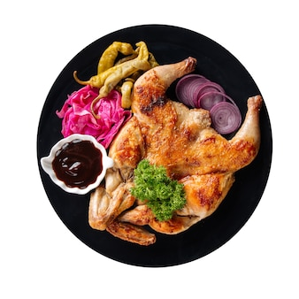 Na białym tle talerz tabaka kurczaka z sosem