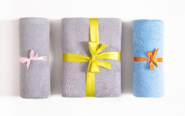 Na białym tle trzy zwinięte i złożone ręczniki frotte związane różową, pomarańczową i żółtą wstążką. niebieskie i szare ręczniki frotte na białym tle. widok z góry.