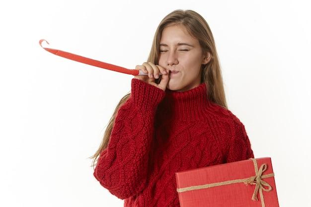 Na białym tle ujęcie emocjonalnej uroczej nastolatki ubrana w stylowy sweter z dzianiny, pozowanie, trzymając fantazyjne czerwone pudełko i dmuchający w gwizdek na przyjęciu urodzinowym, zamierza dać prezent swojej przyjaciółce