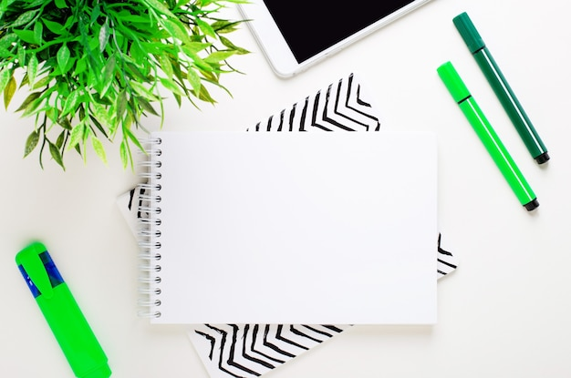 Na białym tle zielone znaczniki, zielona roślina, telefon i pusty notatnik z miejscem na wstawienie tekstu lub ilustracji.