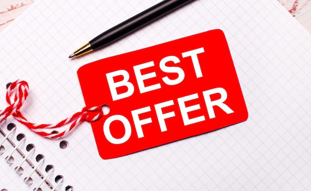 Na białym zeszycie czarny długopis i czerwona metka z ceną na sznurku z napisem best offer.