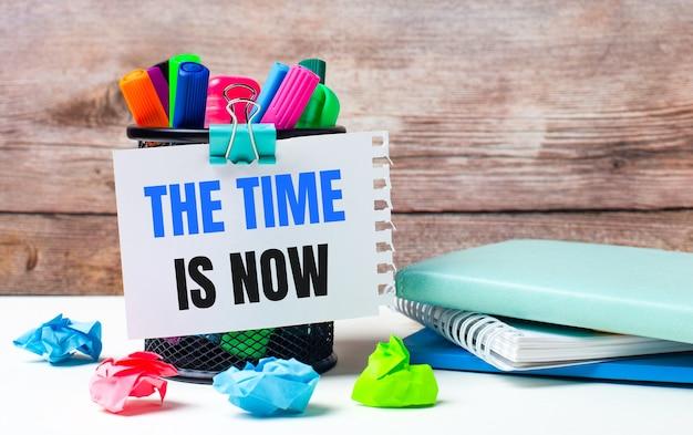 Na biurku i na tle drewnianej ściany stoi stojak z różnokolorowymi flamastrami, jasnymi karteczkami i kartką z napisem the time is now