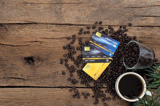 Na biurku leżą karty kredytowe i ziarna kawy. widok z góry