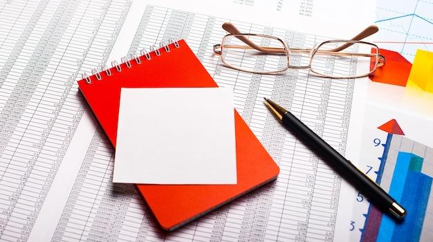 Na biurku okulary w złotych oprawkach, długopis, czerwony zeszyt i czysta biała kartka papieru