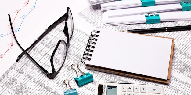 Na biurku są okulary, spinacze do papieru, pusty notatnik i długopis