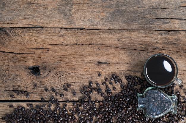 Na biurku stoją kubki i ziarna kawy