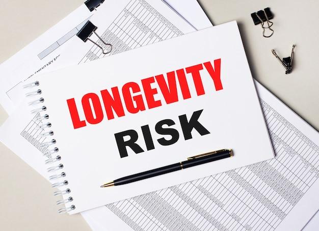 Na biurku znajdują się dokumenty, długopis, czarne spinacze do papieru oraz notes z napisem longevity risk. pomysł na biznes