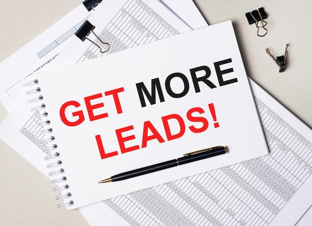 Na biurku znajdują się dokumenty, długopis, czarne spinacze do papieru oraz notes z napisem pobierz więcej leadów. pomysł na biznes