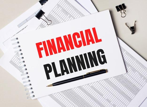 Na biurku znajdują się dokumenty, długopis, czarne spinacze oraz notes z napisem planowanie finansowe. pomysł na biznes