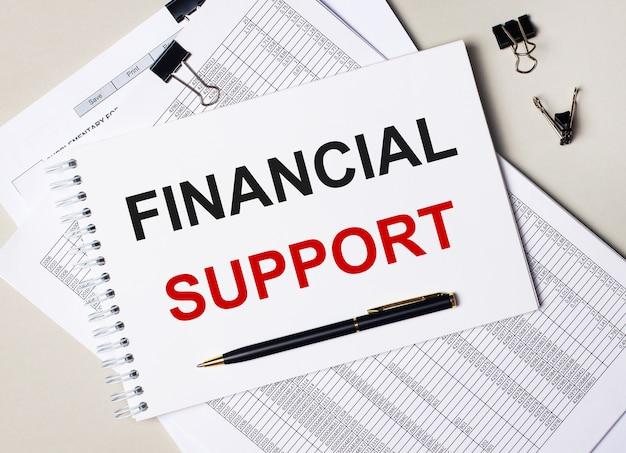 Na biurku znajdują się dokumenty, długopis, czarne spinacze oraz notes z napisem wsparcie finansowe. pomysł na biznes