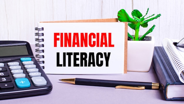Na biurku znajdują się kalkulator, pamiętniki, roślina doniczkowa, długopis i zeszyt z napisem finansowa literacja. pomysł na biznes. miejsce pracy z bliska