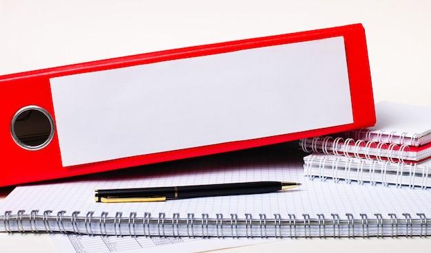 Na biurku znajdują się notatniki, długopis i czerwona teczka na dokumenty z miejscem na wpisanie tekstu. szablon. pomysł na biznes