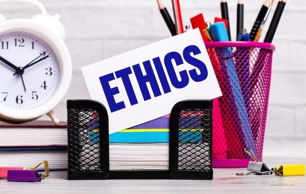 Na biurku znajdują się pamiętniki, budzik, artykuły papiernicze oraz biała kartka z napisem etyka. pomysł na biznes.
