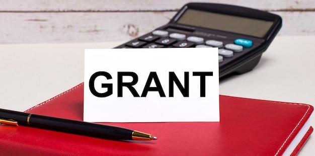 Na biurku znajduje się bordowy zeszyt, kalkulator, długopis i biała kartka z napisem grant. pomysł na biznes.
