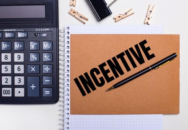 Na biurku znajduje się kalkulator, długopis i spinacze do bielizny obok notesu z napisem incentive