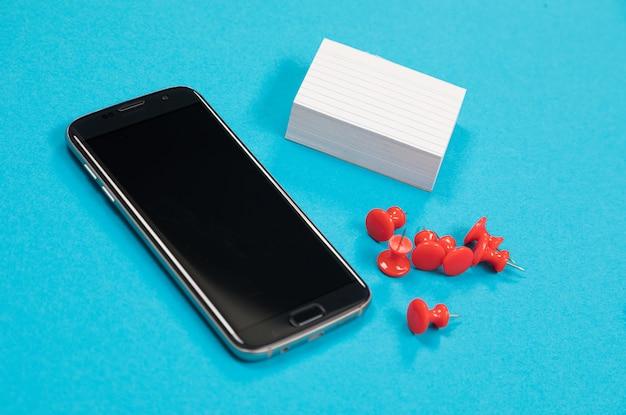Na bladoniebieskiej powierzchni na białym tle leży czarny telefon komórkowy, stos białego papieru i czerwone pinezki