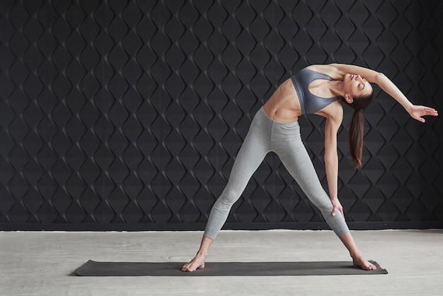 Na bok. dziewczyna z dobrą sylwetką fitness ma ćwiczenia w przestronnym pokoju