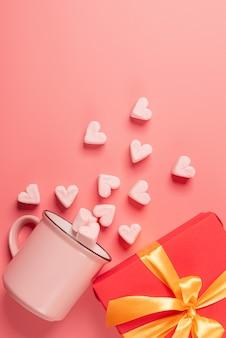 Na boku leży różowy kubek z piankami posypanymi w formie serduszek i prezentu