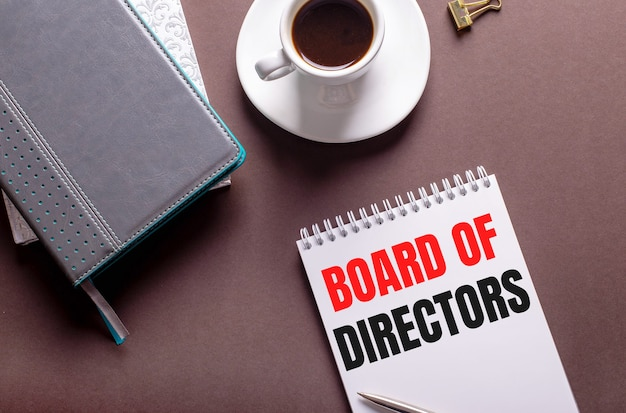 Na brązowej powierzchni pamiętniki, biała filiżanka kawy i zeszyt z radą dyrektorów