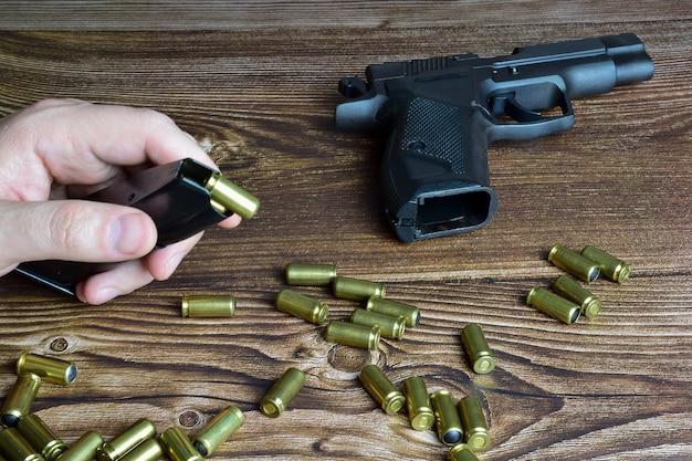 Na brązowym drewnianym tle rozrzucone są traumatyczne naboje i pistolet. ręce wkładają naboje do klipsa pistoletowego