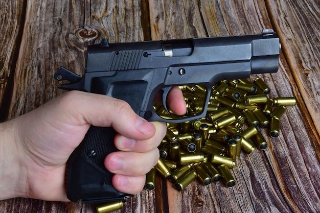 Na brązowym drewnianym tle ułożono stos traumatycznych nabojów. na ich tle ręka trzyma pistolet