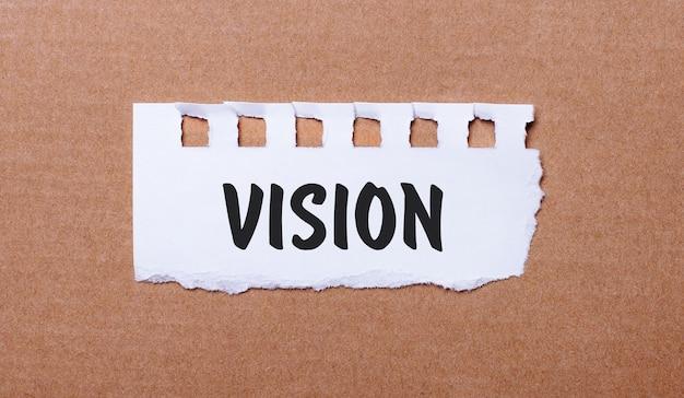 Na brązowym tle biały papier z napisem vision