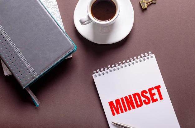 Na brązowym tle pamiętniki, biała filiżanka kawy i notes z mindsetem