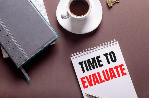 Na brązowym tle pamiętniki, biała filiżanka kawy i zeszyt z napisem time to evaluate