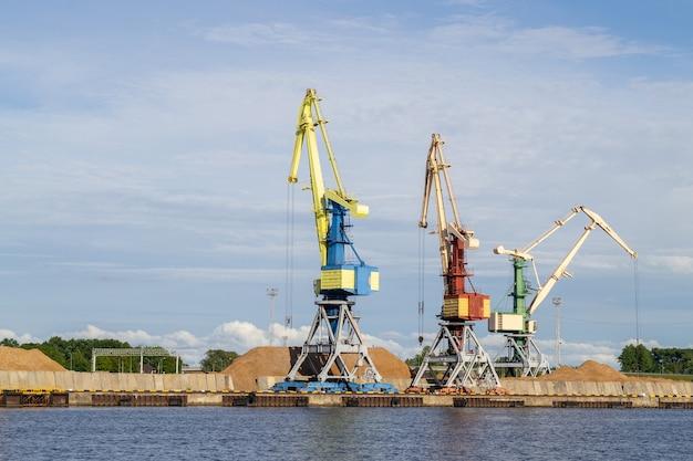 Na brzegach rzeki venta stoją trzy wysokie dźwigi towarowe.