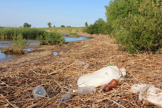 Na brzegu leżą plastikowe butelki, torby i śmieci. odpady, brud, zanieczyszczenie środowiska.