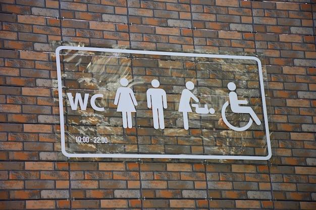 Na ceglanej ścianie znajduje się znak z różnymi symbolami oznaczającymi toaletę