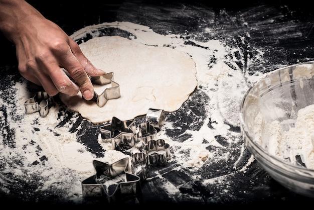 Na ciastka. zbliżenie na ręce młodych mans przy użyciu formy piekarniczej podczas gotowania i pracy w restauracji.