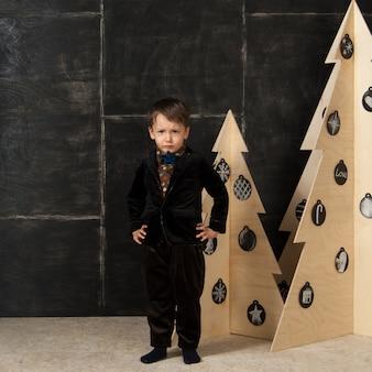 Na ciemnym tle mały chłopiec pozujący w stylowym stroju obok choinki wykonanej z drewna