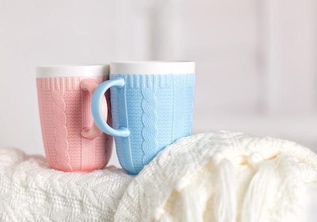 Na ciepłym białym dzianinowym kocu znajduje się kilka filiżanek z wzorem dziewiarskim, różowym i niebieskim
