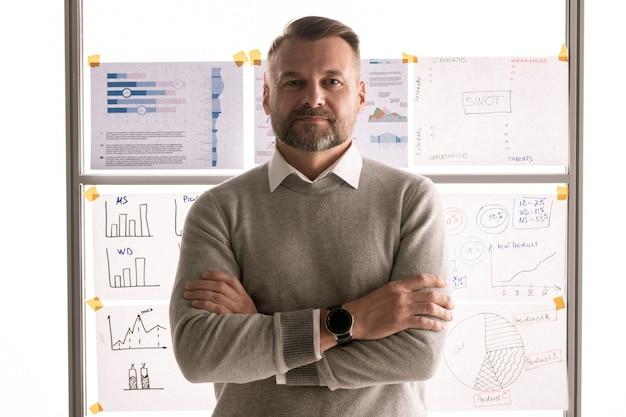Na co dzień dojrzały biznesmen krzyżujący ramiona przy piersi, stojąc przed tablicą z dokumentami
