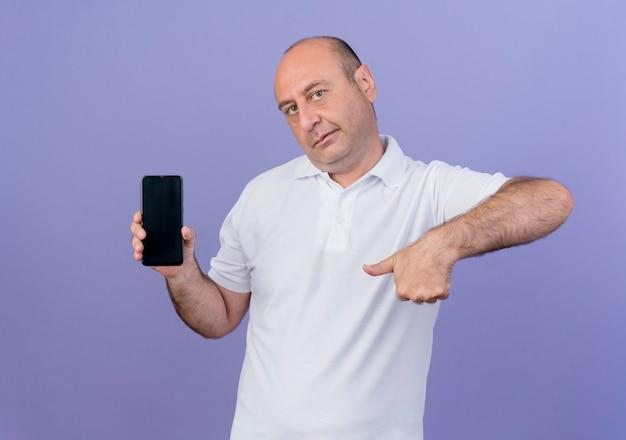 Na co dzień dojrzały biznesmen patrząc na kamery pokazujące telefon komórkowy i wskazując na to trzymając telefon komórkowy na białym tle na fioletowym tle