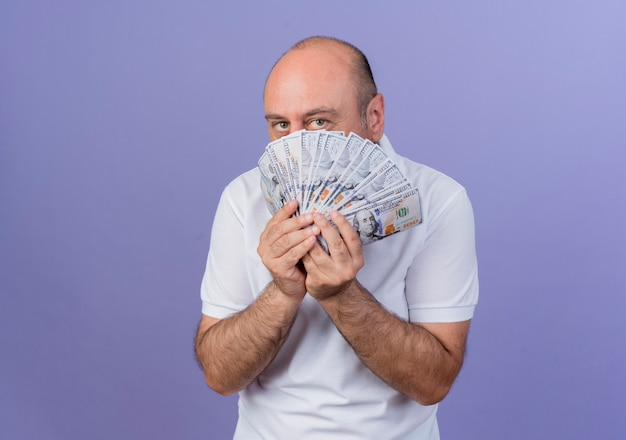 Na co dzień dojrzały biznesmen trzymając pieniądze i patrząc na kamery od tyłu pieniądze na białym tle na fioletowym tle z miejsca na kopię