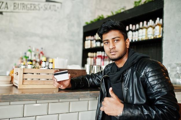 Na co dzień i stylowy młody mężczyzna azji nosić skórzaną kurtkę, siedząc na pasku i posiadania karty kredytowej do zapłaty
