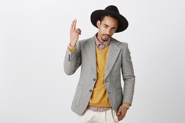 Na co patrzysz. pewny siebie przystojny ciemnoskóry mężczyzna w czarnym kapeluszu i szarej kurtce, pokazujący gest pistoletu i podnoszący rękę