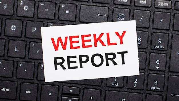 Na czarnej klawiaturze komputera znajduje się biała kartka z napisem raport tygodniowy. widok z góry