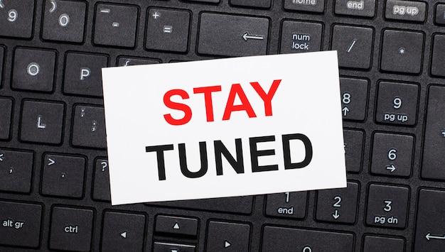 Na czarnej klawiaturze komputera znajduje się biała kartka z napisem stay tuned. widok z góry