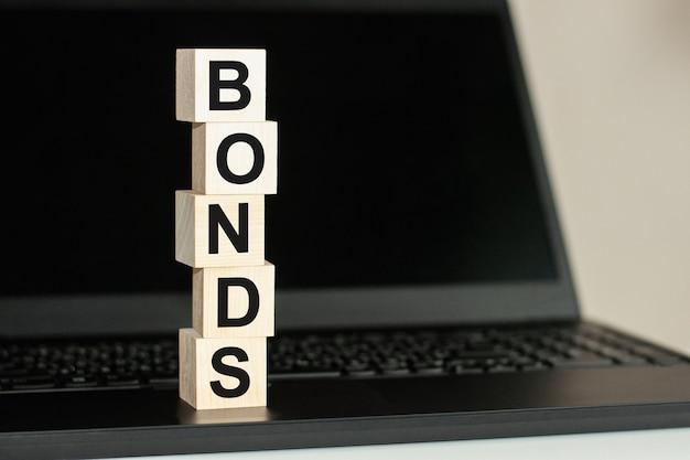 Na czarnej klawiaturze znajduje się rząd drewnianych kostek z napisem bonds napisanym czarną czcionką