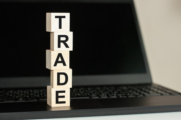 Na czarnej klawiaturze znajduje się rząd drewnianych kostek z napisem trade napisanym czarną czcionką