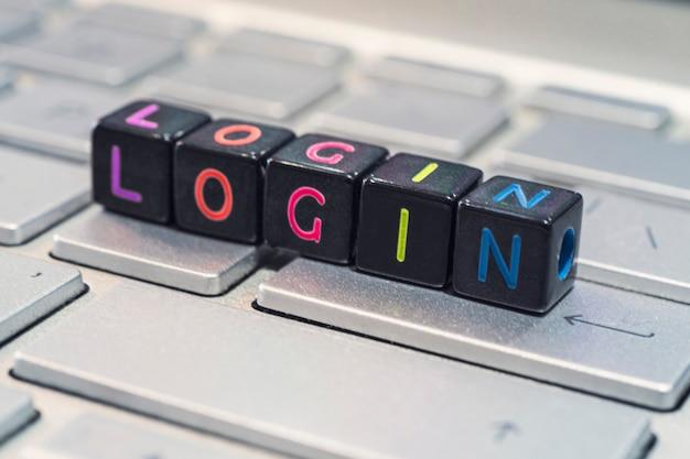Na czarnych kostkach leżących na szarej klawiaturze jest to słowo login. pojęcie technologii informacyjnej i internetu.