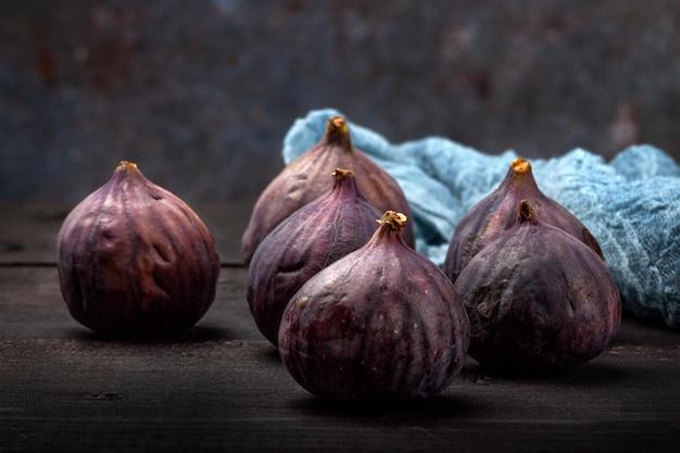 Na czarnym drewnianym stole znajdują się owoce świeżych fig. piękne niebieskie owoce rys. z bliska
