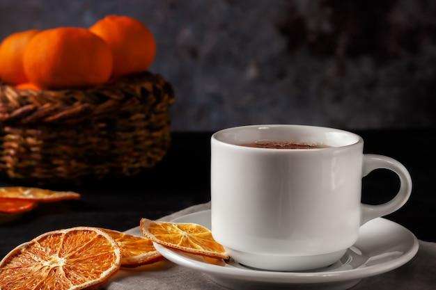 Na czarnym drewnianym tle filiżanka herbaty z suszonymi plasterkami pomarańczy