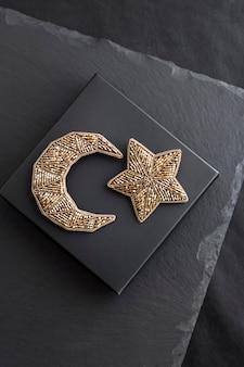 Na czarnym pudełku haftowane koraliki w kształcie księżyca i gwiazdy